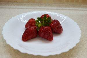 red ripe strawberries on a white plate